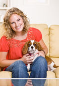 Woman sitting on sofa with dog — Stock Photo