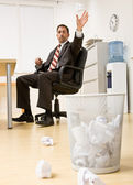 Businessman throwing paper in trash basket — Stock Photo