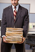 Businessman carrying stack of file folders — Stock Photo