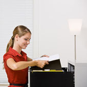 Businesswoman putting file in file cabinet — Stock Photo