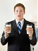 Businessman holding paper coffee cups — Stock Photo