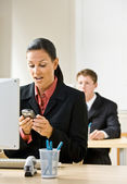 Businesswoman text messaging on cell phone — Stock Photo