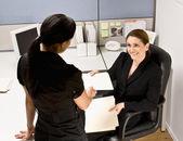 Businesswoman handing co-worker file folder — Stock Photo