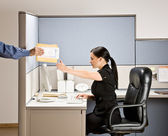 Businesswoman multi-tasking at desk in cubicle — Stock Photo