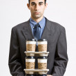 Businessman carrying stack of coffee cups — Stock Photo