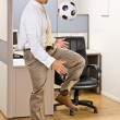 Businessman playing with soccer ball in office — Stock Photo #18802653