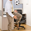 Businessman playing with soccer ball in office - Stock Photo