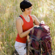 Woman opening backpack in field — Stock Photo #18802769
