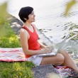 Woman using laptop near pond — Stock Photo #18802779