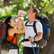 Couple with backpacks drinking water — Stock Photo