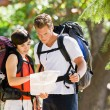 Couple with backpacks looking at map — Stockfoto #18802823