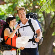 Couple with backpacks looking at map — Stock Photo