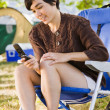 Camper text messaging on cell phone — Stock Photo