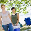 Stock Photo: Women carrying cooler at campsite
