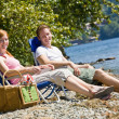 Couple having picnic near stream — Stock Photo
