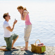 Boyfriend proposing to girlfriend near stream - Stock Photo