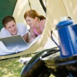 Couple laying in tent with laptop — Stock Photo
