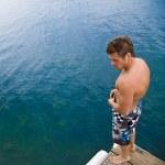 Man standing on pier at lake — Stock Photo