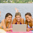 Friends laying on pier using laptop — Stock Photo