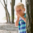 Stock Photo: Boy hiding behind tree