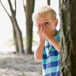 Boy hiding behind tree - Stock Photo
