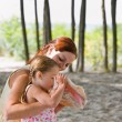 Mother watching daughter blow into seashell - Stock Photo