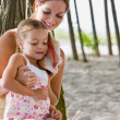 Stock Photo: Mother and daughter listening to seashell