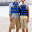 Stock Photo: Couple wearing life jackets at beach
