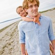 Father giving daughter piggy back ride at beach — Stock Photo