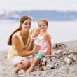 Mother and daughter listening to seashell at beach — Stock Photo