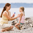 Mother applying sunscreen to daughter at beach — Stock Photo #18803645