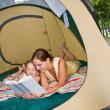 Mother reading to daughter in tent — Stock Photo