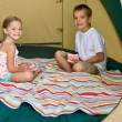 Brother and sister playing cards in tent — Stock Photo