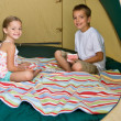 Royalty-Free Stock Photo: Brother and sister playing cards in tent