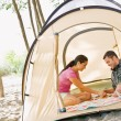 Couple playing boardgame in tent - Stock Photo