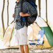 Stock Photo: Mcarrying backpack at campsite
