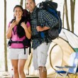 Couple carrying backpacks at campsite — Zdjęcie stockowe #18803721