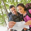 Couple in backpacks looking at map — Stock Photo