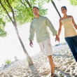 Stock Photo: Couple walking holding hands at beach