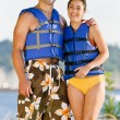 Couple wearing life jackets at beach — Stock Photo