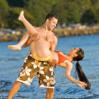 Stock Photo: Boyfriend lifting girlfriend on beach