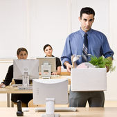 Fired businessman carrying box — Stock Photo