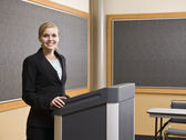 Young Woman Standing at Podium Smiling — Stock Photo