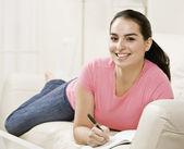 Ung kvinna skriva i tidning — Stockfoto