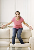 Young Woman Standing on Couch — Stock Photo