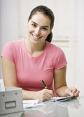 Young Woman Writing Check — Stock Photo