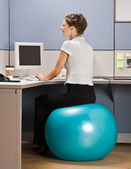 Businesswoman sitting on exercise ball at desk — Stock Photo