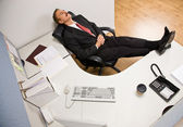 Businessman sleeping at desk with feet up — Stock Photo