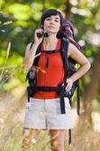 Curious woman with backpack and binoculars — Stock Photo