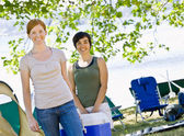 Women carrying cooler at campsite — Stock Photo